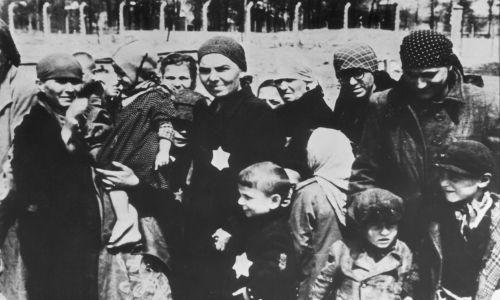 """Ok. 1943 r oku, Auschwitz. Żydowskie kobiety i dzieci, z naszytymi na piersiach żółtymi """"Gwiazdami Dawida"""", w trakcie selekcji. Wiele z nich wysyłano do zagazowania lub na eksperymenty medyczne, także te prowadzone w Auschwitz przez najbardziej znanego lekarza-rzeźnika Josefa Mengele. Fot. Hulton Archive / Getty Images"""