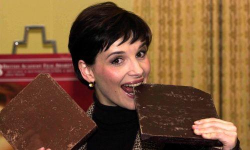 """Juliette Binoche zanurza zęby w wielkich tabliczkach czekolady w Claridges Hotel w centrum Londynu, po tym, jak dowiedziała się, że otrzymała nominację do Oscara w kategorii najlepszej aktorki za rolę w filmie """"Czekolada"""", opartym na powieści brytyjskiej autorki Joanne Harris. (Fot. Fiona Hanson - PA Images / PA Images via Getty Images"""