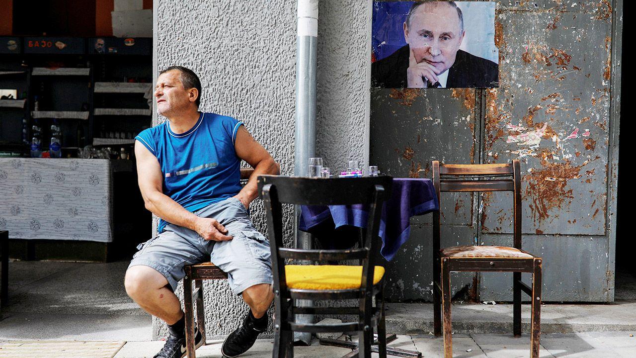 Kosovska Mitrovica. Mężczyzna siedzi obok zdjęcia prezydenta Rosji Władimira Putina (fot. REUTERS/Marko Djurica)