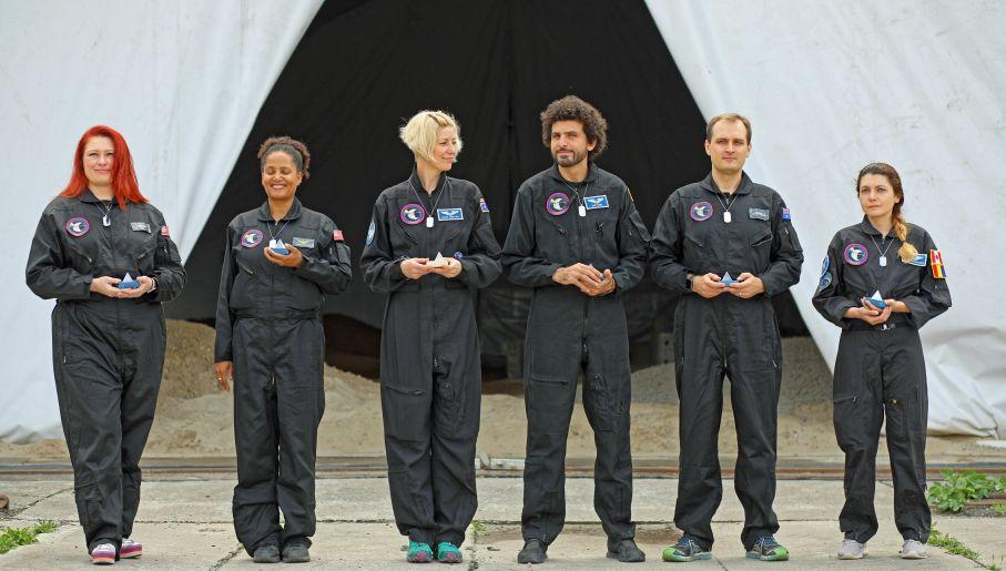 """Naukowcy biorący udział w symulacji przed modelem księżycowej bazy kosmicznej """"Habitat Lunares"""" na starym lotnisku w Pile, 29 lipca (fot. PAP/Marek Zakrzewski)"""