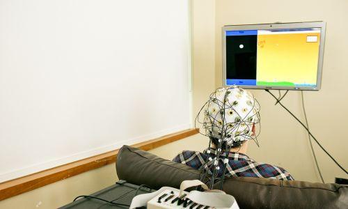 Nadawca jest podłączony do elektroencefalograficznej maszyny odczytującej aktywność mózgu. Komputer przetwarza sygnały mózgowe i wysyła impulsy elektryczne przez sieć do odbiornika na terenie kampusu. Fot. Mary Levin, University of Washington
