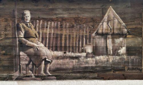 Dubno w gminie Boćki, nad rzeką Nurzec. Jeden z pierwszych murali Arkadiusza Andrejkowa na Podlasiu. W tym przypadku nie poznał historii tej kobiety, ani nie korzystał ze starej rodzinnej fotografii, tylko ze zdjęcia Jerzego Rajeckiego – znanego fotografa Podlasia. Zamieszkały w Białymsgtoku, a urodzony w Hajnówce jest autorem wystaw i albumów utrwalających znikający świat: drewnianą architekturę, krzywe płoty, babcie w chustkach, ławeczki sąsiedzkie, czy pelargonie w dubeltowych oknach. Fot. AA