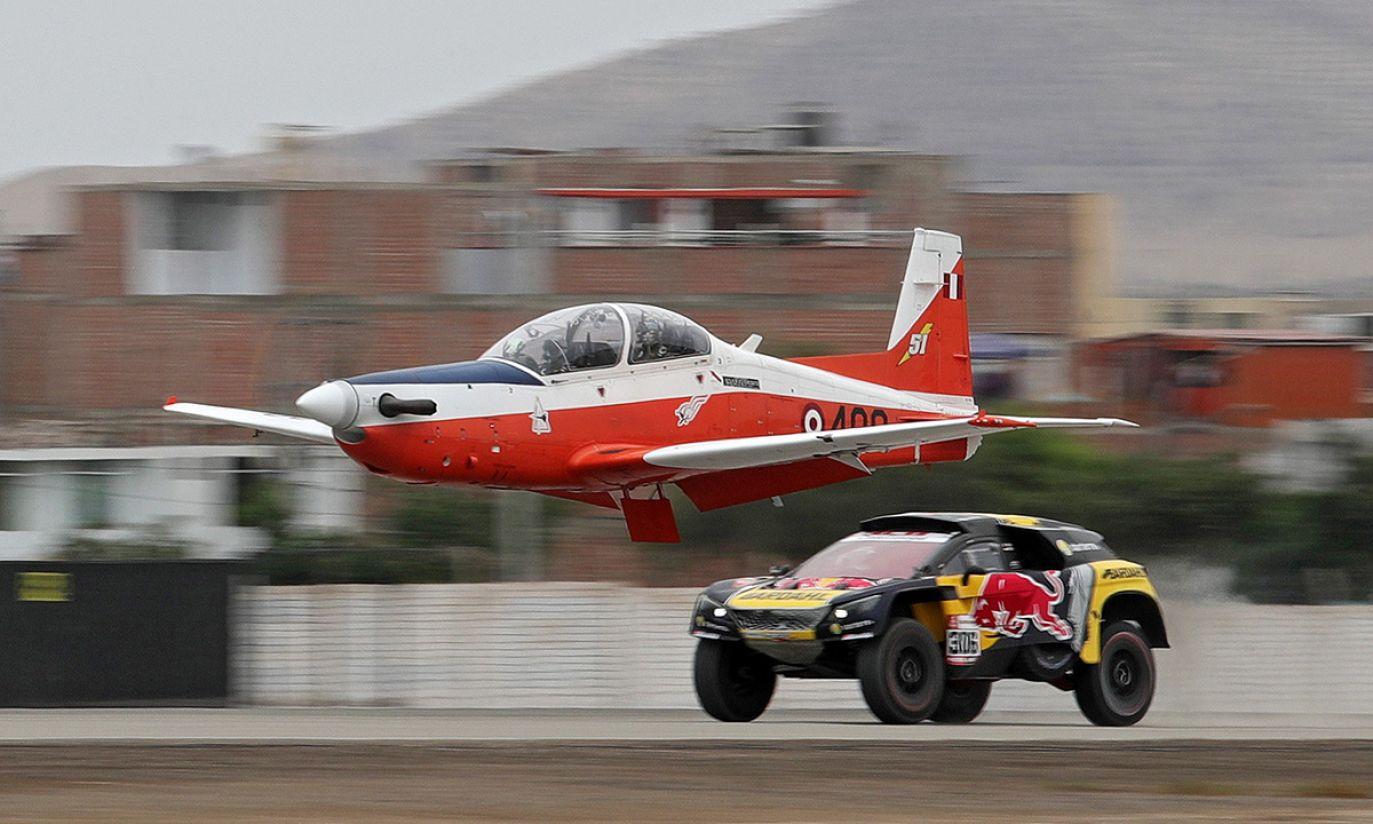 Francuski kierowca Sébastien Loeb w Peugeocie 3008 DKR i samolot szkoleniowy KT-1P podczas pokazu przed startem rajdu (fot. PAP/EPA/Ernesto Arias)
