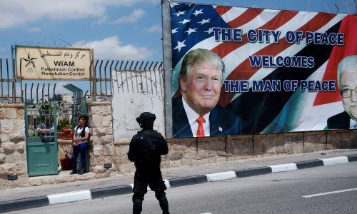 Żołnierz stoi na straży, a ludzie patrzą, jak prezydent Stanów Zjednoczonych Donald Trump wraca do Jerozolimy po spotkaniu z prezydentem Autonomii Palestyńskiej Mahmudem Abbasem w mieście Betlejem na Zachodnim Brzegu. 23 maja 2017. Fot. REUTERS / Jonathan Ernst