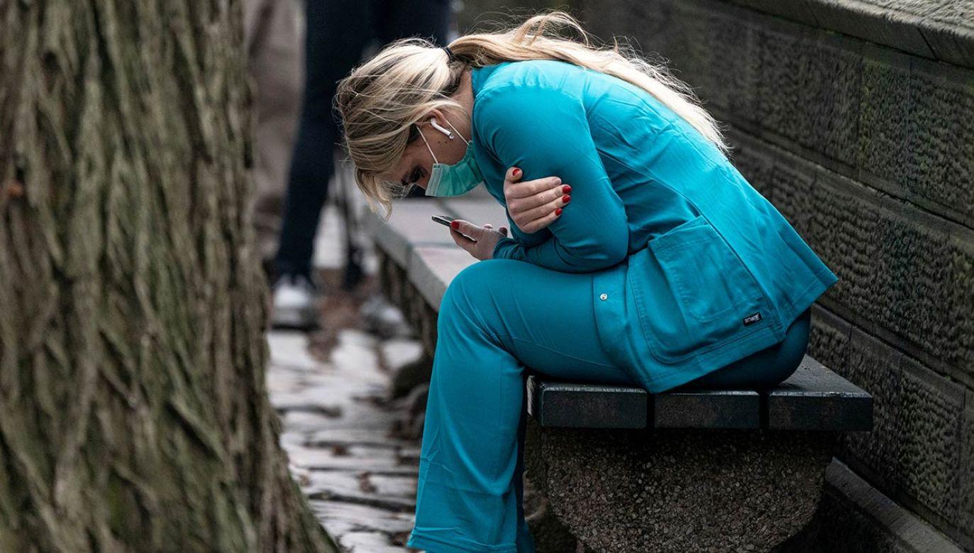 Pracownica służby zdrowia na ławce w okolicach Central Parku na Manhattanie w Nowym Jorku, 30 marca 2020 r. Fot. REUTERS/Jeenah Moon     TPX IMAGES OF THE DAY - RC2NUF9VY5KU