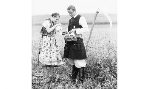 Prosty posiłek po żniwach. Kobieta nalewa do kubka zapewne mleko lub kompot, mężczyzna trzyma koszyk z jedzeniem – na ogół to były głównie proste dania z mąki czy roślin, dziś zyskujące często status kuchni regionalnej. Minimum składników, maksimum kaloryczności, na ogół z mąki i ugotowanych ziemniaków, ubitych na gładką masę, czasem razem z kapustą, z dodatkiem cebuli, skwarek, czasem śmietaną. Lata 1919 – 1939. Fot. NAC/IKC, sygn. 1-G-2462-6