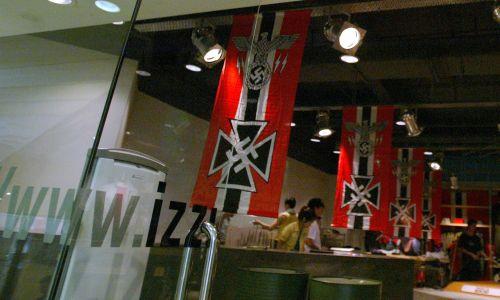 """Sklep IZZUE w Hongkongu. Marka promowała w 2003 r. swoją linię ubrań z motywami nazistowskimi, wykorzystując flagi i filmy propagandowe III Rzeszy. Po protestach wydała oświadczenie, iż """"projektant nie zdawał sobie sprawy, że nazistowskie symbole będą uważane za obraźliwe"""". Nazwa marki brzmi jak angielskie słowo """"Problem"""", a jej koncern ma sklepy w całej Azji, m.in. w  Tajlandii, Malezji i Chinach, Arabii Saudyjskiej. Jest także w Niemczech. Fot. Antony Dickson / South China Morning Post via Getty Images"""